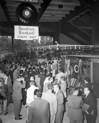 Gente reunida durante exposición de llantas en una agencia automotríz