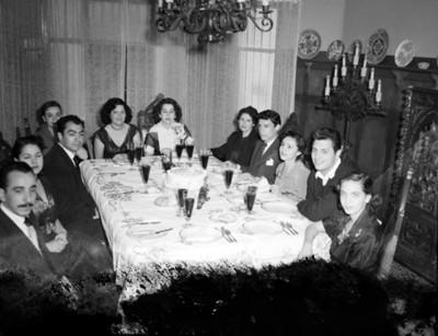 Familia reunida en el comedor de una casa festejan cumpleaños, retrato de grupo