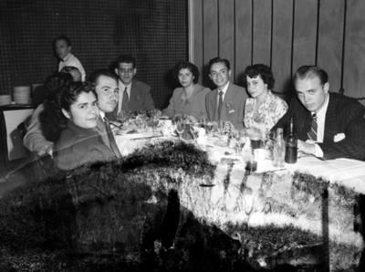 Hombres y mujeres en comedor de un salón durante banquete, retrato de grupo