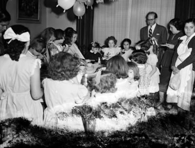 Niñas en el comedor de una casa durante fiesta de cumpleaños