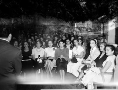 Mujeres sentadas en el salón de una tienda departamental observan a un hombre