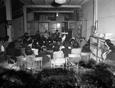 Mujeres observan a músicos tocar guitarra en el salón de una tienda