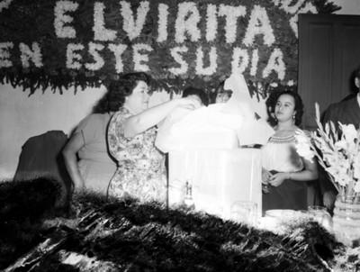 Mujer coloca copa sobre un regalo durante fiesta en un salón