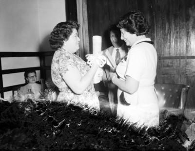Mujer recibe regalos en la sala de una casa