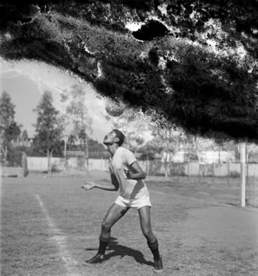 Futbolista domina el balón con la cabeza en un campo deportivo