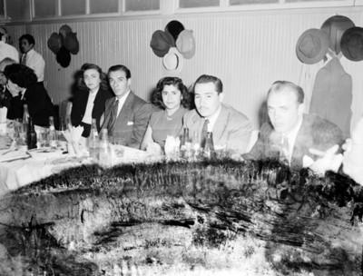 Hombres y mujeres durante banquete en un salón, retrato de grupo