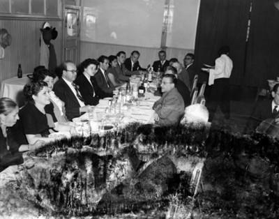 Hombres y mujeres durante banquete en un salón