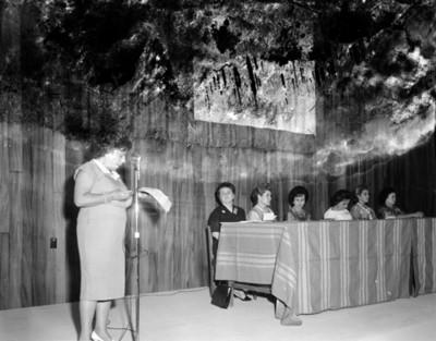 Mujer de pie frente a micrófono lee discurso durante convención