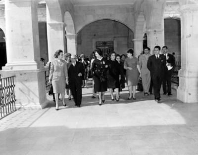 Eva Samano de López Mateos jutno a otras personas caminan por el pasillo de un edificio