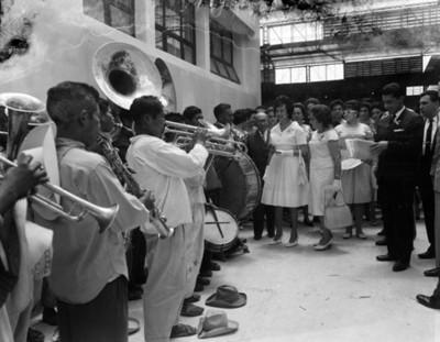 Eva Samano de López Mateos y gente escuchan a banda musical en las instalaciones de una empacadora de alimentos