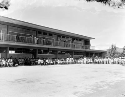 Gente en el patio de una escuela durante festival escolaren un auditorio