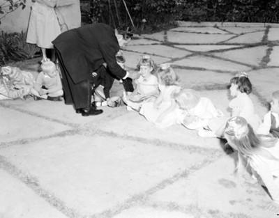 Hombre entrega ave a una niña durante fiesta infantil en el patio de una casa