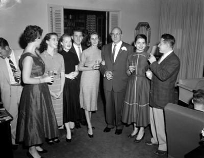 Hombres y mujeres de pie en sala de una casa durante reunión social, retrato de grupo