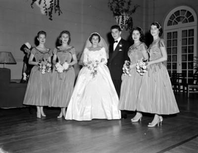 Novios y mujeres de pie en un salón durante boda, retrato de grupo