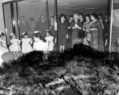 Eva Samano de López Mateos, hombres y mujeres observan a niñas durante juego infantil en una escuela