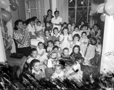 Niños durante fiesta de cumpleaños en la sala de una casa, retrato de grupo