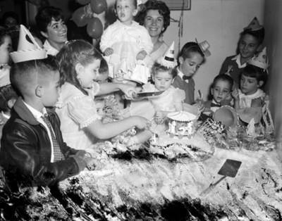 Niña parte pastel durante fiesta de cumpleaños en una casa