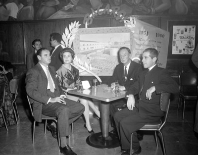 Hombres y mujer en una mesa durante fiesta