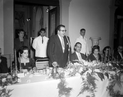 Hombre de pie frente a micrófono pronuncia discurso durante banquete en un salón