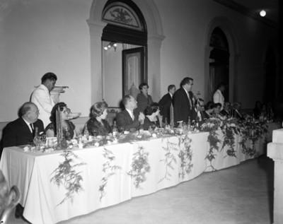 Hombre frente a micrófono pronuncia discurso durante banquete en un salón