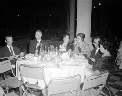 Hombres y mujeres en comedor durante banquete en un salón