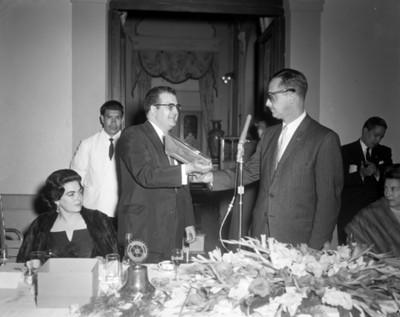 Hombre recibe obsequio durante banquete en un salón