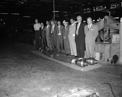 Hombres junto a pieza de máquinaria en una instalación industrial