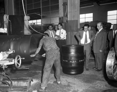 Hombres observan a obrero trabajar durante visita a instaleción industrial