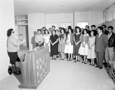 Maestros, mujeres y hombres durante clase de piano