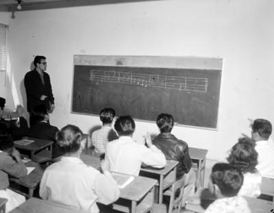 Maestro y alumnos durante clase de música en un salón