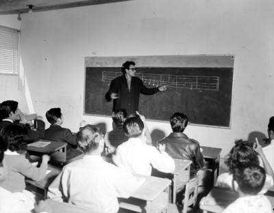 Profesor enseña notas musicales a alumnos