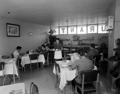 Mujer lleva una charola en una cafetería