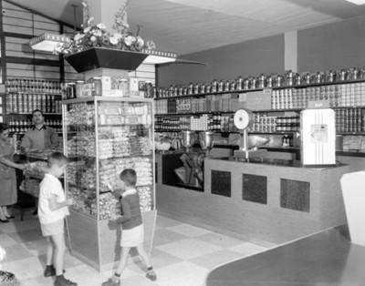 Niños cogen dulces del mostrador de una tienda