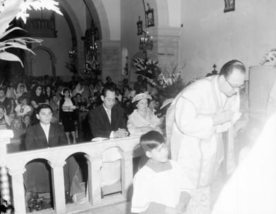 Sacerdote y gente durante misa en una iglesia