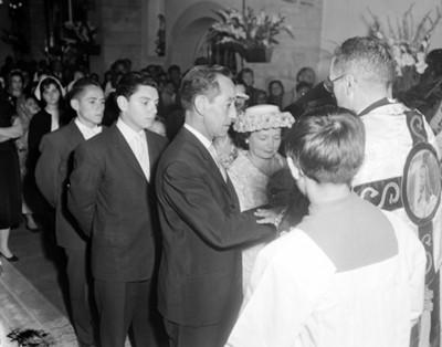 Sacerdote y gente durante ceremonia religiosa en el interior de una iglesia