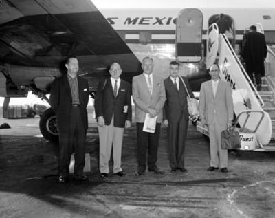 Empresarios junto a un avión en aereopuerto, retrato de grupo