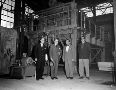 Hombres junto a máquinas en instalación industrial