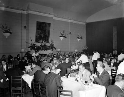 Hombres durante banquete en un salón, vista general