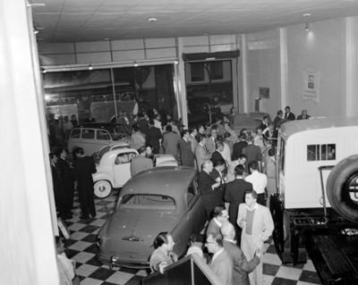 Gente durante exhibición de camiones y automóviles en una agencia, vista general
