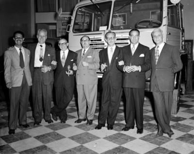 """Hombres frente a camión """"DINA"""" en una agencia automotríz, retrato de grupo"""