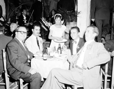 Mesera sirve bebidas a hombres, retrato de grupo