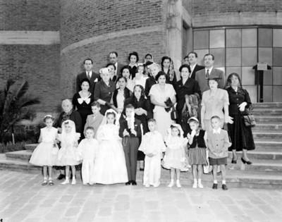 Familia durante ceremonia de primera comunión, retrato de grupo