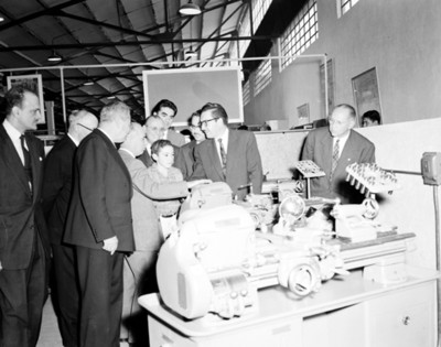 Empresarios observan máquina en un taller
