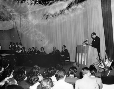 Eva Samano de López Mateos observa a un hombre pronunciar discurso durante duranate conferencia en un auditorio