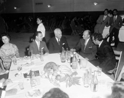 Ejecutivos y mujeres conversan durante banquete en un taller automotríz