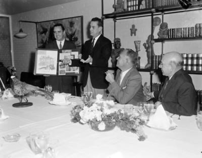 Hombre muestra carteles de publicidad durante una reunión