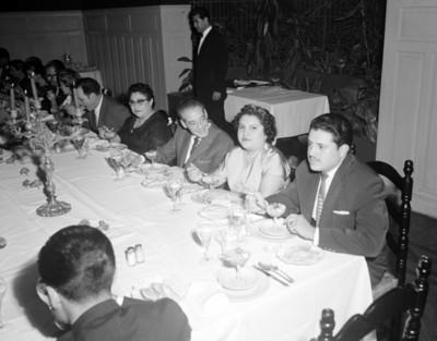 Hombres y mujeres durante un banquete