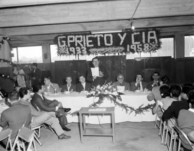 Hombre pronuncia discurso durante conferencia de G. Prieto y Cía