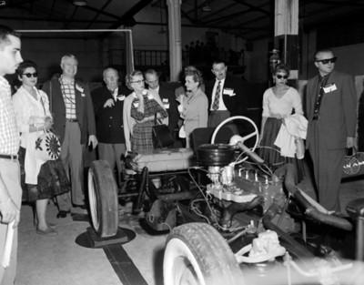 Empresarios y mujeres observan motores en exhibición automotríz