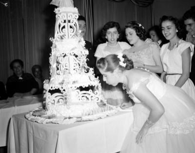 Quinceañera sopla velas de un pastel durante fiesta